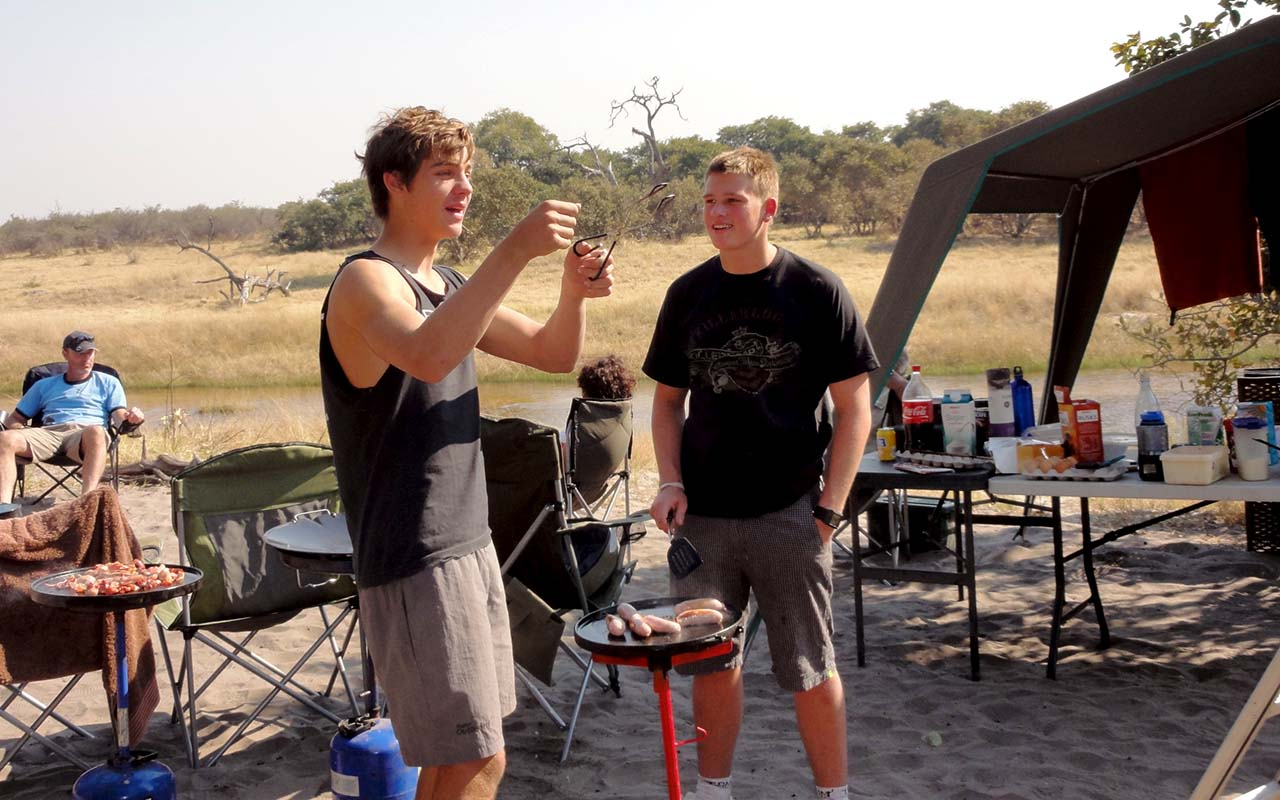 Preparing breakfast, and a story in between, at Paradise campsite, Savuti